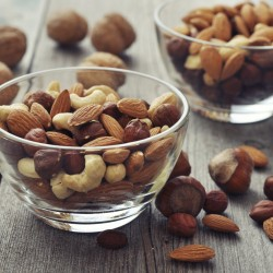 Almonds, walnuts, cashew and hazelnuts in glass bowls on wooden background
